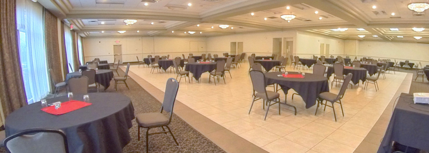 Socially distanced tables and chairs in a hotel banquet hall.