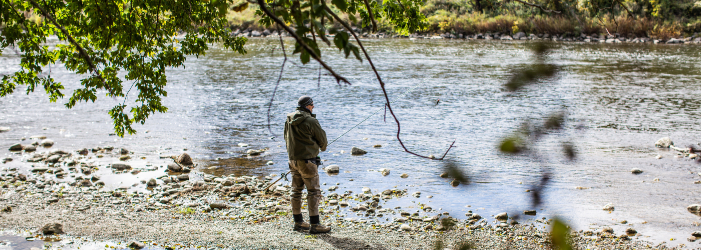 Man stands fishing at the bank of the Grand River.