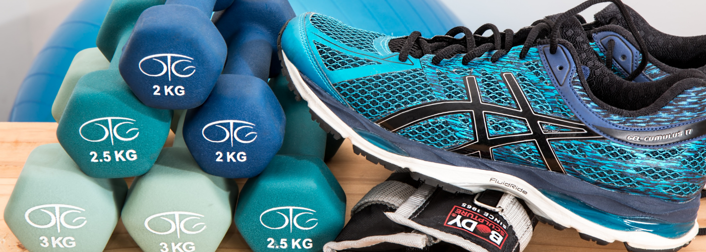 Blue dumbells, running shoes and weight anklet piled neatly.