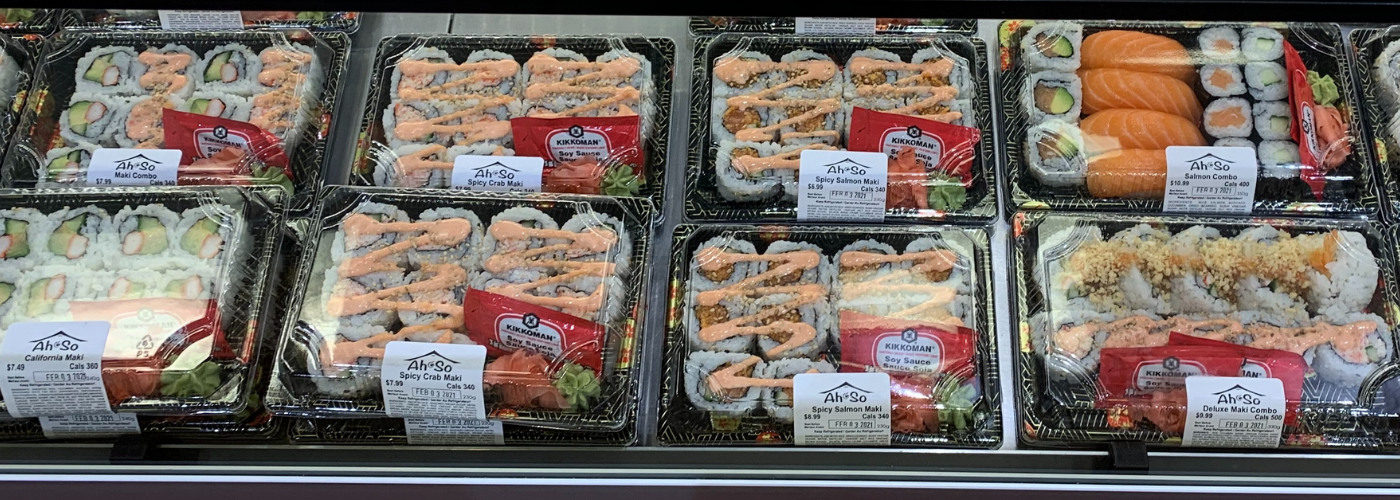 Lunch sized sushi packages in a grocery display.
