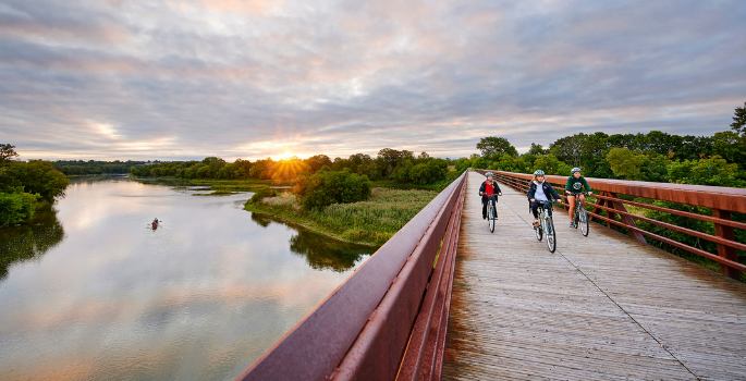 Three people bike on a bridge over the Grand River.